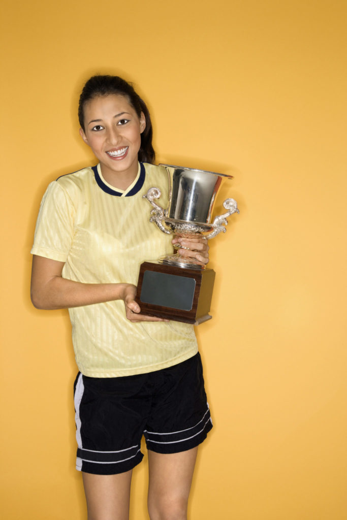 Smiling girl holding trophy.